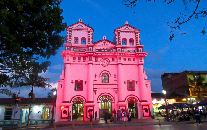 Iron Roamer, Brian Thiessen, in Guatape Colombia looking onto the church lit up in pink at night.